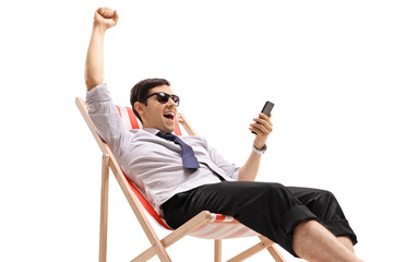 Businessman sunbathing looking at a phone and gesturing happiness