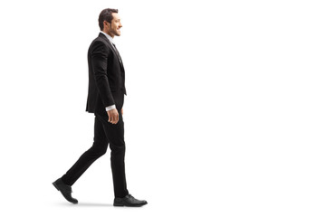 Young man in a suit walking and smiling