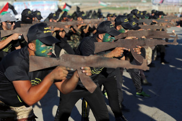 Young Palestinians aim wooden rifles as they demonstrate their skills during a military-style graduation ceremony at a summer camp organised by Islamic Jihad, in Gaza City