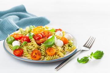 Fototapete - healthy fusilli pasta with pesto sauce, roasted tomatoes, mozzarella