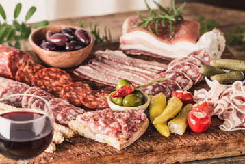Variety of appetizer on wooden board, wine snack set with prosciutto, salami, ham, olives.