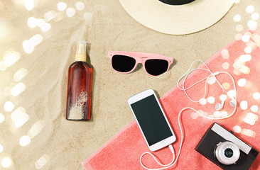vacation and summer holidays concept - smartphone with earphones and film camera on towel, straw...