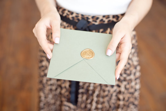 Close-up photo of female hands holding a silver blue or pink invitation envelope with a wax seal, a gift certificate, a postcard, a wedding invitation card