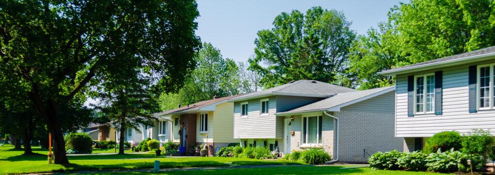 Panorama of sunlit small suburban houses
