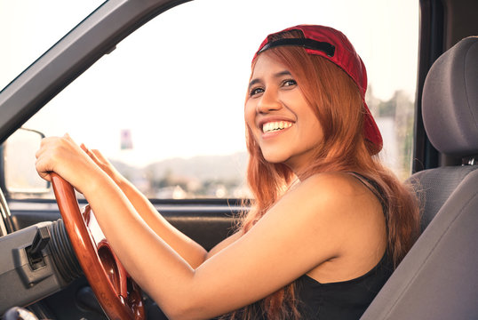 Asian trendy cool woman driving car with bright sun - Happy ethnic diverse Thai girl inside vehicle travelling on fun summer road trip - Holiday, vacation & millennial generation activity - face focus