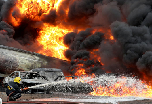 Fireman targets water hose at the base of a fire after a pipeline fire erupted in Ijegun area of Lagos
