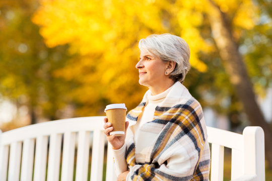 old age, retirement and people concept - portrait of senior woman drinking takeaway coffee at autumn park