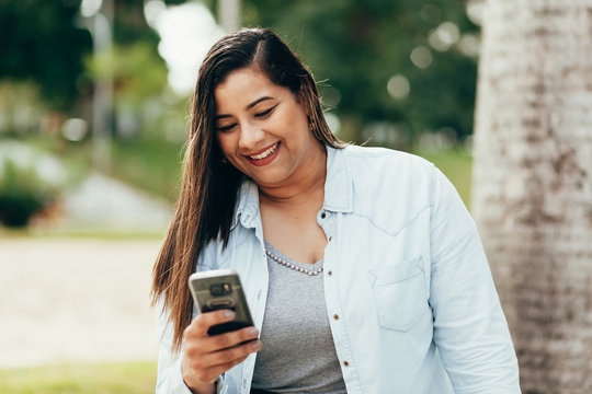 Portrait of beautiful plus size woman using her smartphone outdoors