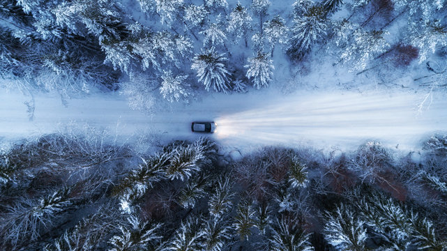 Aerial view of night winter road and car in forest. Drone shot.