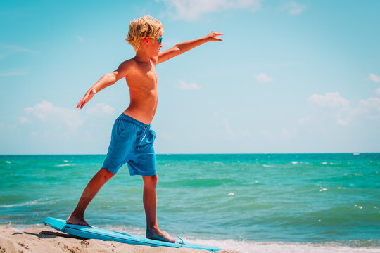 young boy learning to surf at sea beach