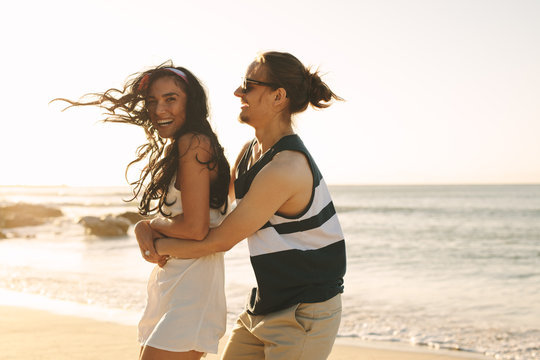 Playful young couple on beach vacation