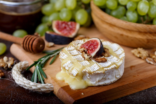 Baked Camembert on wooden board, grapes, figs, nuts, honey, herbs
