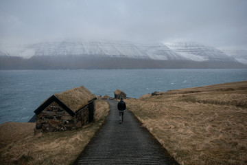 Man walking on a road to the sea in Faroe Islands