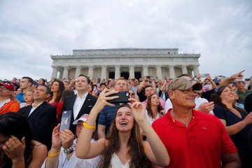 """Attendees take photos during the """"Salute to America"""" event during Fourth of July Independence Day celebrations at the Lincoln Memorial in Washington"""