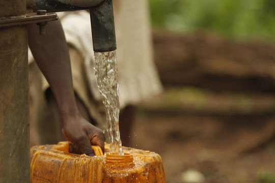 Filling Water jug with Well Water in Sierra Leone Africa