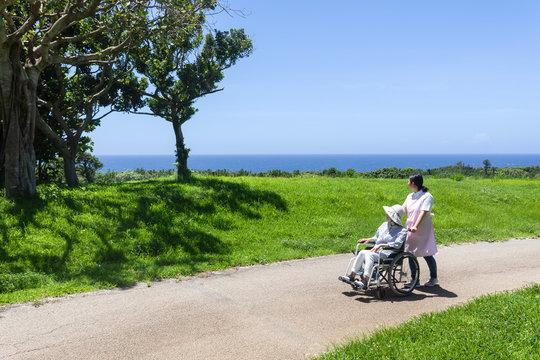 車いすで散歩するシニアと介護ヘルパー