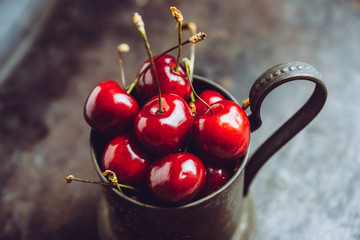 Ripe and juicy cherries in old metal cup on the dark rustic background. Selective focus. Shallow depth of field.