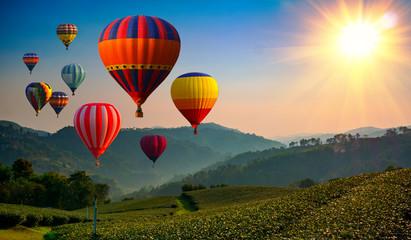 Poster Ballon Hot air balloon above high mountain at sunrise or sunset.