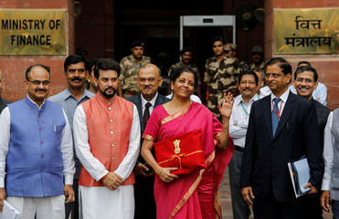 India's Finance Minister Nirmala Sitharaman (C) gestures during a photo opportunity as she leaves her office to present the federal budget in the parliament in New Delhi