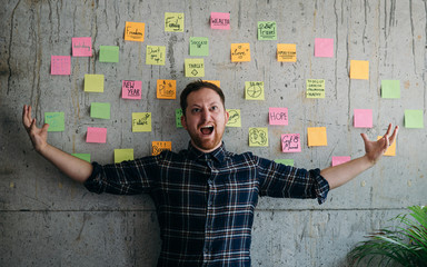 Happy man present his sticky notes chart on cement wall.  Entrepreneur concept
