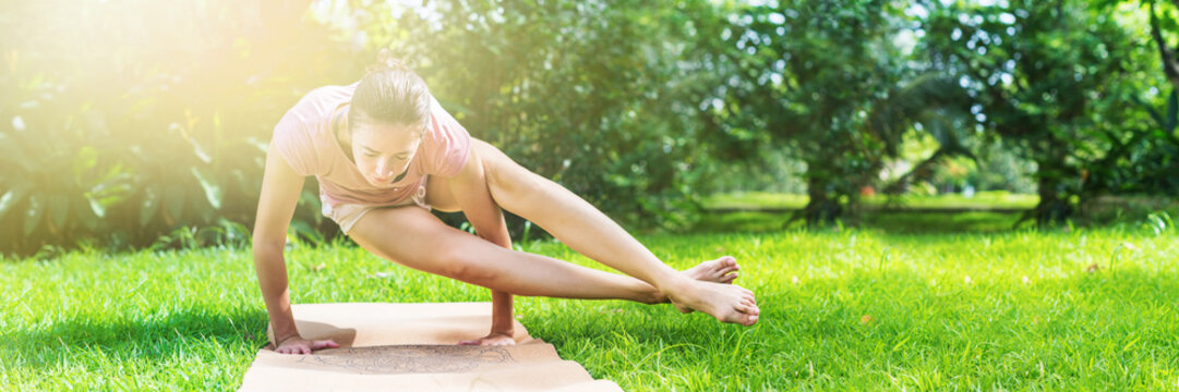 Girl doing yoga on open air on natural meadow