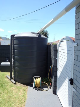Rain collection water tank installed in a suburban house
