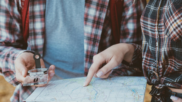 Wanderlust and adventures. Cropped shot of travelers using compass and map to explore country.