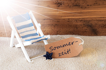 Sunny Summer Label With Sand And Aged Wooden Background. German Text Sommerzeit Means Summertime. Deck Chair For Holiday Or Vacation Feeling.