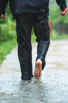 A man in the rain is barefoot in puddles