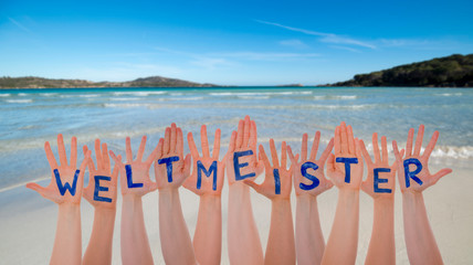 Many Hands Building German Word Weltmeister Means World Champion. Beautiful Beach, Ocean And Sea As Background