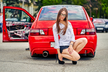 girl in glasses sits on the background of a red car audio show