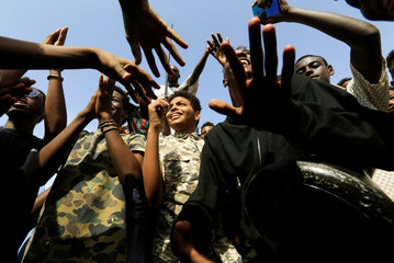 Sudanese people chant slogans as they celebrate, after Sudan's ruling military council and a coalition of opposition and protest groups reached an agreement to share power during a transition period leading to elections, along the streets of Khartoum