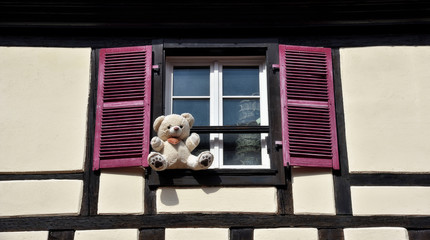 Lovely teddy bear sitting at a window-sill at a half-timbered house.