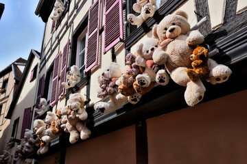 Lovely teddy bears sitting hanging at a half-timbered house.