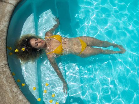Girl in yellow bikini floats in the pool with rubber ducklings.