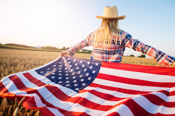 American female farmer in casual clothing with arms spread open holding USA flag in wheat field. Wall mural