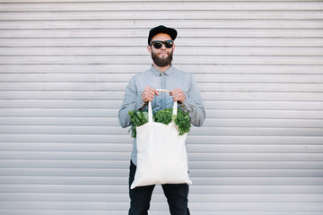 Man holding an eco bag filled with grocery. Vegetables and fruits are hanging from the bag. Ecology concept of environment protection