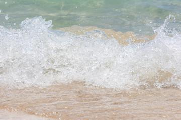 Macro shot of some sea waves hitting the beach