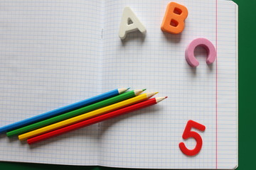 ABC-the first letters of the English alphabet and colored pencils on the school notebook, score...
