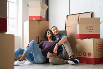 Multiethnic couple in new home with boxes