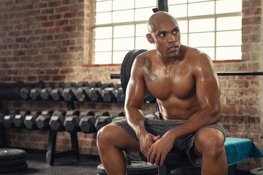 Muscular sweaty man resting in gym