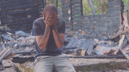 Portrait of a sad man on the background of a burned house, after fire . Consequences of fire disaster accident. Ruins after fire disaster, despair concept. Fotomurales