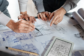 Real-estate concept, Two engineer and architect discussing blueprints data working and digital tablet on construction building project