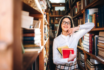 people, knowledge, education and school concept - happy student girl or young woman with book posing in an old library