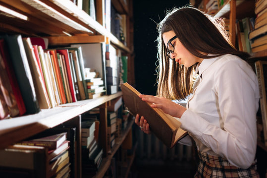people, knowledge, education and school concept - student girl or young woman reading a book in the old library
