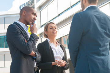 Mix raced couple of company representatives meeting business partner outdoors. Man and woman in office suits talking to colleague. Business communication concept