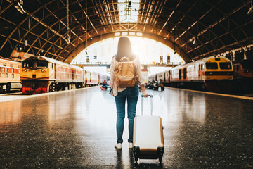 woman traveler standing with luggage at train station.