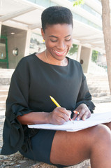 Smiling delighted female artist enjoying leisure time outside. Peaceful African American woman sitting on stairs and drawing with pencils in album. Drawing concept
