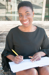 Happy designer enjoying drawing outside. Cheerful African American woman sitting on stairs, holding color pencils and open album and smiling at camera. Inspiration concept