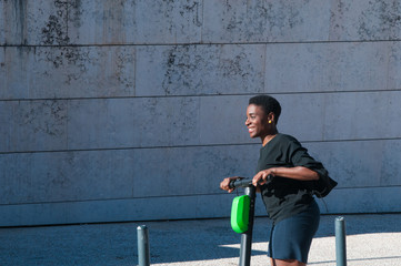 Happy black woman riding electric scooter outdoors. Young woman wearing casual blouse and skirt with building wall in background. Modern transportation concept.